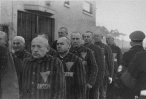 Ένστολοι κρατούμενοι, που φέρουν στα ρούχα τους τριγωνικά σήματα, συναθροίζονται υπό τη συνοδεία Ναζί φρουρών στο στρατόπεδο συγκέντρωσης Σαξενχάουζεν. Σαξενχάουζεν, Γερμανία, 1938. — National Archives and Records Administration, College Park, Md. Πηγή: http://www.ushmm.org/outreach/el/media_ph.php?ModuleId=10007720&MediaId=893