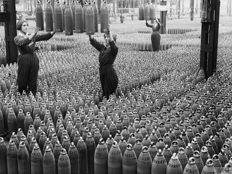 Η πολεμική προσπάθεια στα μετόπισθεν. Γυναίκες εργάτριες σε πολεμικό εργοστάσιο στη Βρετανία. Με τον ίδιο τρόπο που θα μπορούσαν να κρατούν το μωρό τους, κρατούν τις οβίδες πυροβολικού. Πηγή: Αυτοκρατορικό Μουσείο Πολέμου του Λονδίνου (Imperial War Museum).