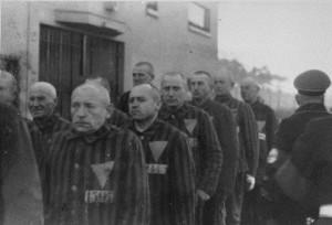 Ένστολοι κρατούμενοι, που φέρουν στα ρούχα τους τριγωνικά σήματα, συναθροίζονται υπό τη συνοδεία Ναζί φρουρών στο στρατόπεδο συγκέντρωσης Σαξενχάουζεν. Σαξενχάουζεν, Γερμανία, 1938. — National Archives and Records Administration, College Park, Md. Πηγή: https://www.ushmm.org/outreach/el/media_ph.php?ModuleId=10007720&MediaId=893